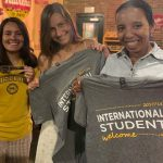 Three students hold up Mizzou T-shirts.