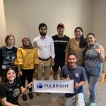 "Fulbright students pose with a ""Fulbright"" banner in a banquet room."