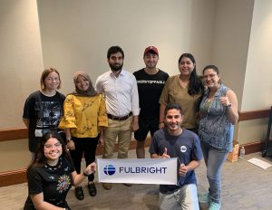 """Fulbright students pose with a """"Fulbright"""" banner in a banquet room."""