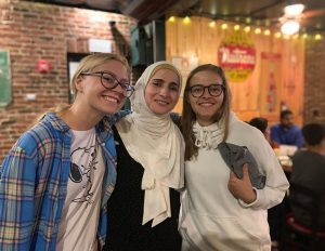 Three female students lean together and smile for the camera inside a local pizza restaurant.