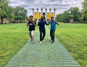 Three students pose with their hands like tiger claws in front MU's six columns on a grassy quad.