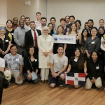 "A large group of people pose with a ""Fulbright"" banner in a banquet room."