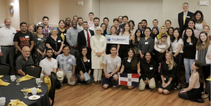 """A large group of people pose with a """"Fulbright"""" banner in a banquet room."""