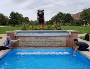 Two students pose on either side of a square fountain with a tiger statue above it.