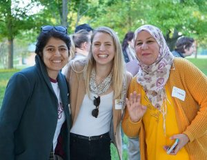 Three women lean together and smile for the camera in a green park.