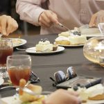 Small plates of delicate desserts sit at the center of a banquet table as people eat the main course.