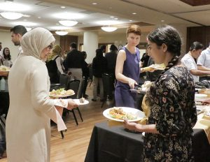 Three women fill their plates from the buffet table while others mingle in the background.