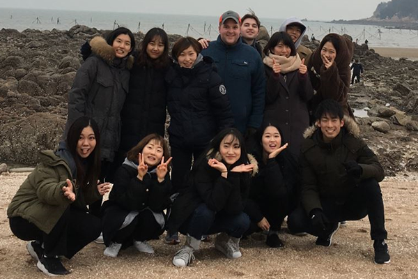 LEAD program alumni pose on a beach on a cloudy day.