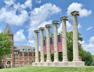 Three american flags hang between the stone columns on the grassy quad.