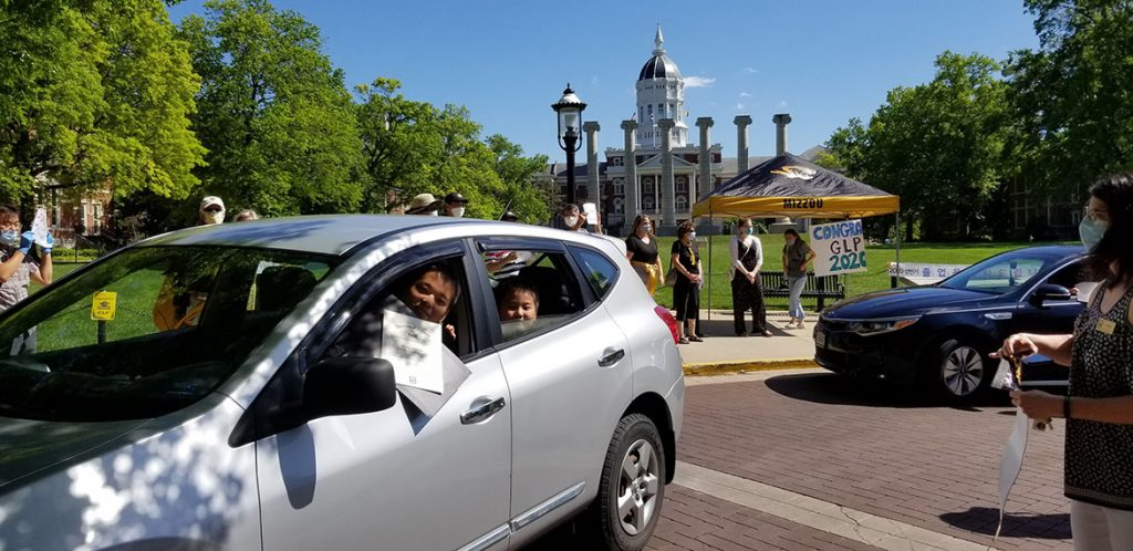 A scholar smiles and holds his certificate out his car window as he drives through the graduation celebration.