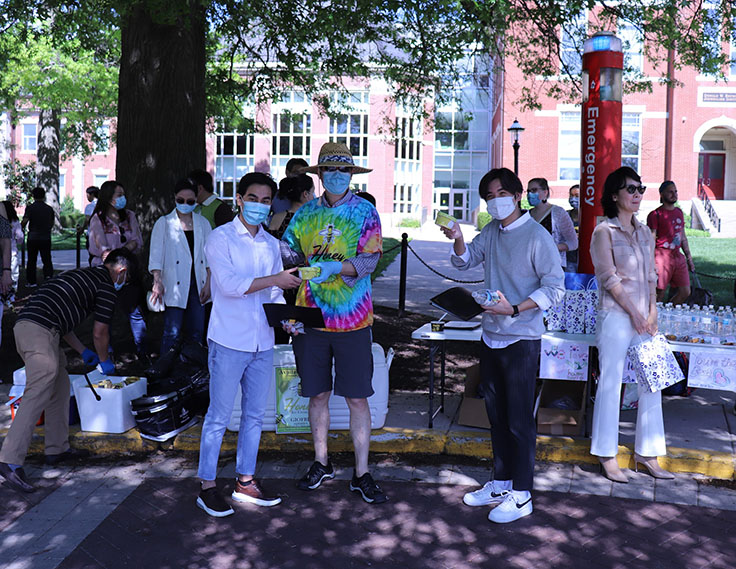 Asian Affairs staff wearing masks pass out ice cream to graduating scholars in the shade of a tree.
