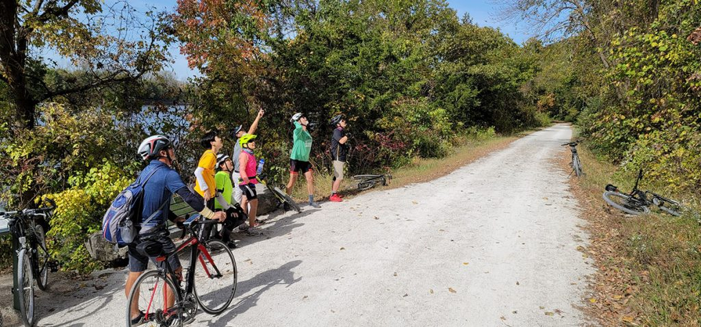 Scholars and staff stand and sit with bikes alongside the gravel trail looking up at something out of frame