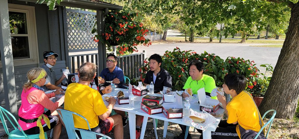 People sit around a table on an outdoor patio each boxed lunches