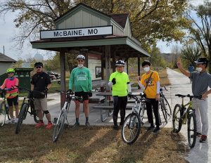 Scholars and staff pose with their bikes alongside a gravel trail; a covered shelter with a sign that reads 'McBaine, MO' is in the background