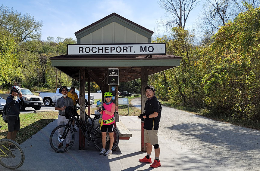 Scholars and staff stand with bikes alongside a gravel trail and under a covered shelter with a sign that reads 'Rocheport, MO'