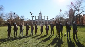 scholars throw their hats in the air in celebration