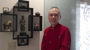 A man wearing red poses by a shelf of Chinese items