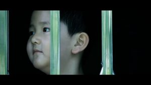 An Asian child's face is seen in profile against a dark background behind green bars.