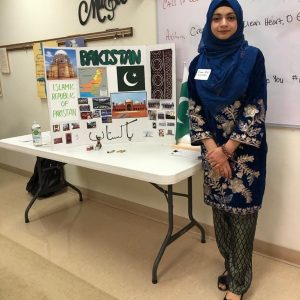 Photo of Kiran Bibi (Global UGRAD IREX), standing beside an informational poster about Pakistan.