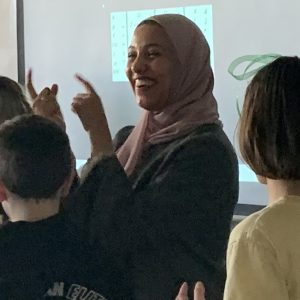 Photo of Sohaila Bakr, smiling and gesturing with her hands as she gives a presentation to elementary school students, who are facing towards her and away from the camera.