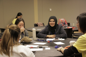 Mahnoor Rizwan smiles as she sits at a table with other international students, chatting with them during international student welcome for spring 2020.