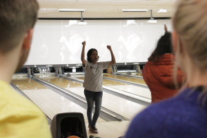 Maria Kale faces the camera, arms raised and face cheering. She is standing in front of a bowling lane at a bowling alley.