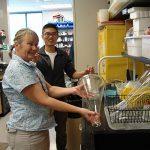Volunteer helps wash glassware in a lab
