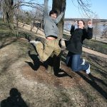 A student and an ambassador jump in a park
