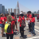 Students in matching red shirts gather around a guide in a parking lot with a suspension bridge and skyscrapers in the background.