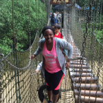 A smiling student crosses a high bridge suspended by chains across a river in the forest.