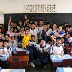 Chinese students in matching jackets pose in front of a blackboard in a classroom.