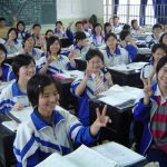 Chinese students wearing matching jackets sit at desks in a classroom and hold up the peace sign for the camera.