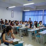 Chinese students sit at tables in rows in a classroom.
