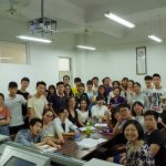 Chinese students pose while standing around a table in a classroom.