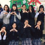 An American teacher poses with a group of Korean students all making a heart symbol with their hands.