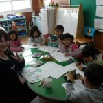 A female student teacher sits at a table with six Korean elementary school students, all coloring pictures.