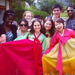 Three American students wear traditional Korea dress and pose with other program participants outside.