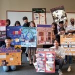 A group of students pose with their presentation posters.