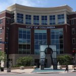 Columbia City Hall, a five story brick building with a key-hole shaped sculpture out front.